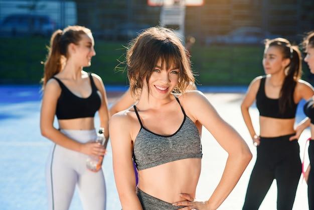 Giovane donna graziosa con la corda di salto sul suo collo che esamina macchina fotografica dopo l'allenamento all'aperto con i suoi amici femminili sui precedenti sullo stadio.