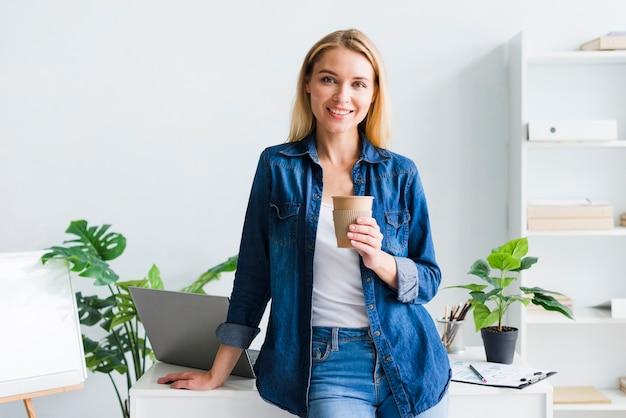 Giovane donna graziosa con la tazza di carta nel posto di lavoro