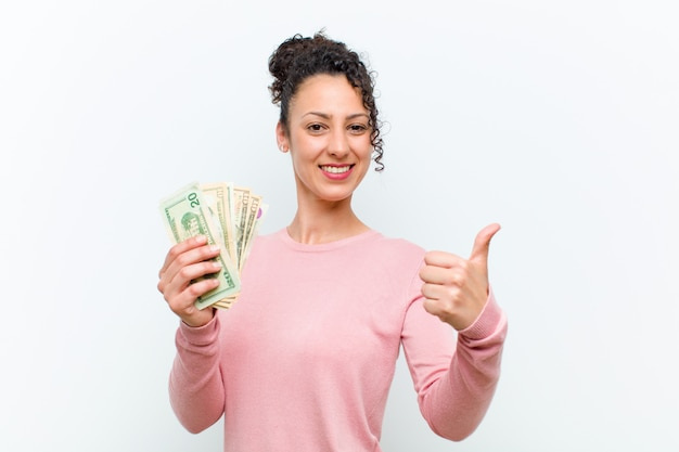 Giovane donna graziosa con le banconote contro il muro bianco