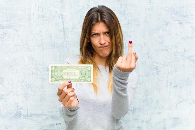 Giovane donna graziosa con le banconote contro la parete del grunge