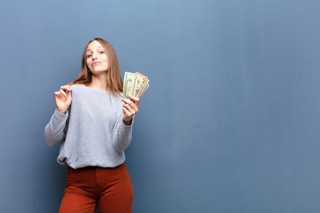 Giovane donna graziosa con le banconote del dollaro contro la parete blu con uno spazio della copia