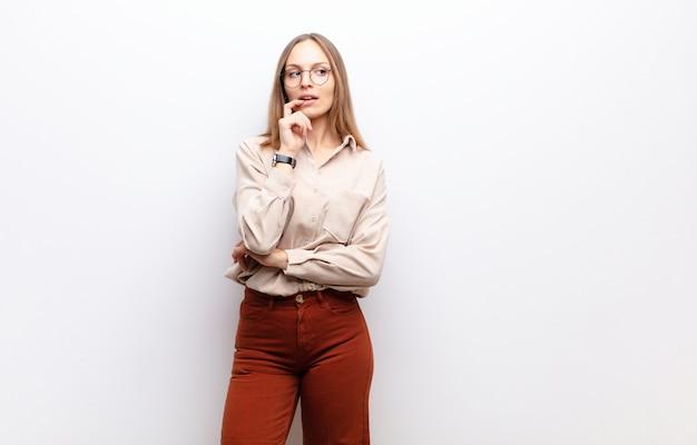 Giovane donna graziosa con lo sguardo sorpreso, nervoso, preoccupato o spaventato, guardando al lato verso lo spazio della copia sopra la parete bianca