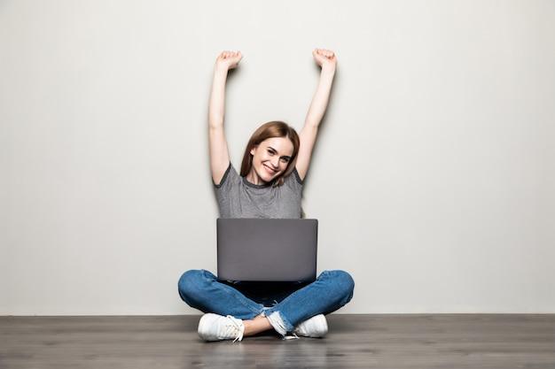 Giovane donna graziosa con un computer portatile che si siede sul pavimento per celebrare una vittoria