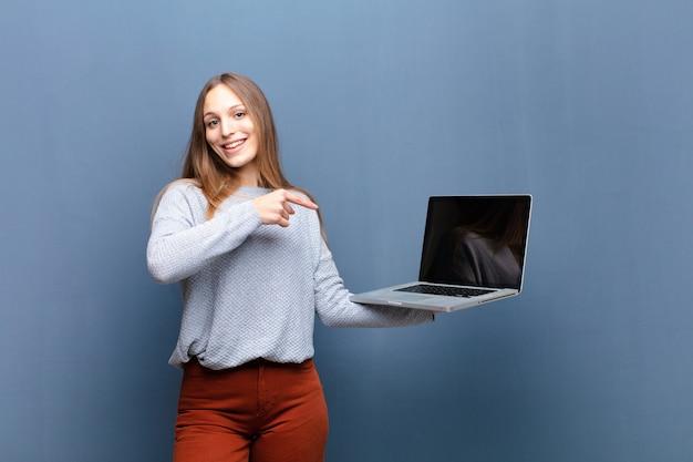 Giovane donna graziosa con un computer portatile contro il blu con un copyspace