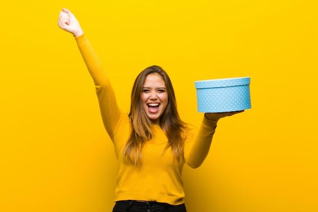 Giovane donna graziosa con un contenitore di regalo contro la parete arancione