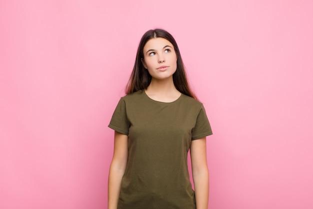 Giovane donna graziosa con un'espressione preoccupata, confusa, all'oscuro, alzando lo sguardo per copiare lo spazio, dubitando contro il muro rosa