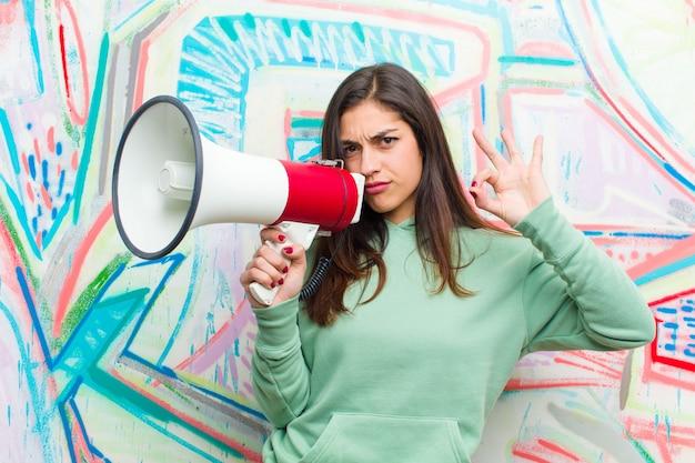 Giovane donna graziosa con un megafono contro il muro di graffiti