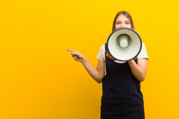 Giovane donna graziosa con un megafono contro l'arancia