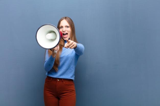 Giovane donna graziosa con un megafono contro la parete blu con uno spazio della copia