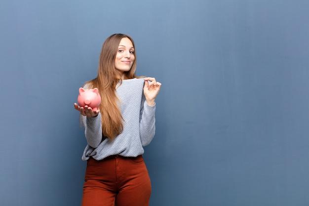 Giovane donna graziosa con un salvadanaio contro la parete blu con uno spazio di copia