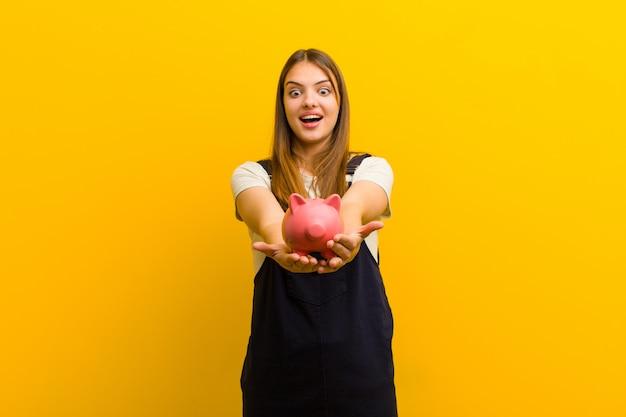 Giovane donna graziosa con un salvadanaio su sfondo arancione