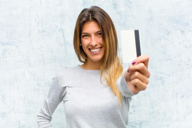 Giovane donna graziosa con una carta di credito