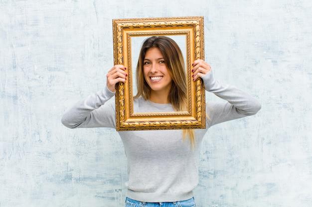 Giovane donna graziosa con una cornice barocca contro la parete del grunge