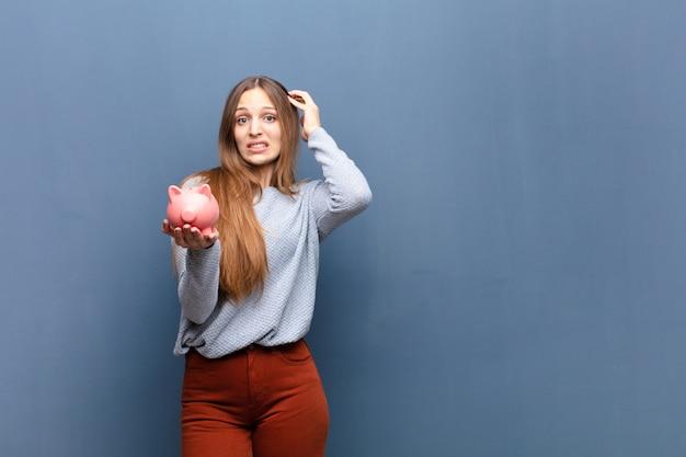 Giovane donna graziosa con una parete blu del porcellino salvadanaio con un copyspace