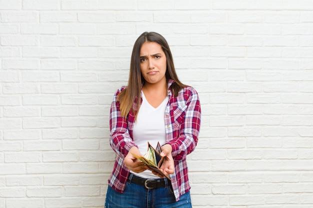 Giovane donna graziosa con una struttura del muro di mattoni del portafoglio