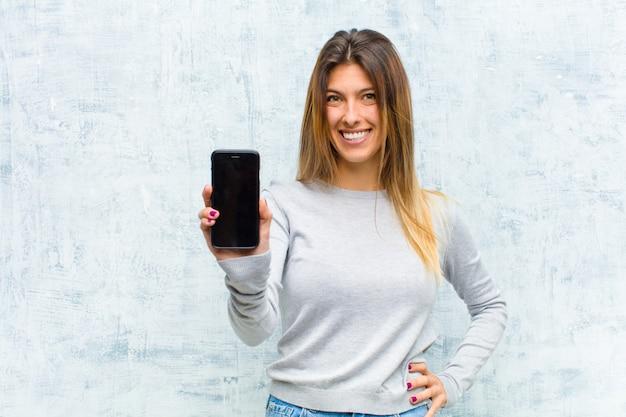 Giovane donna graziosa con uno smart phone