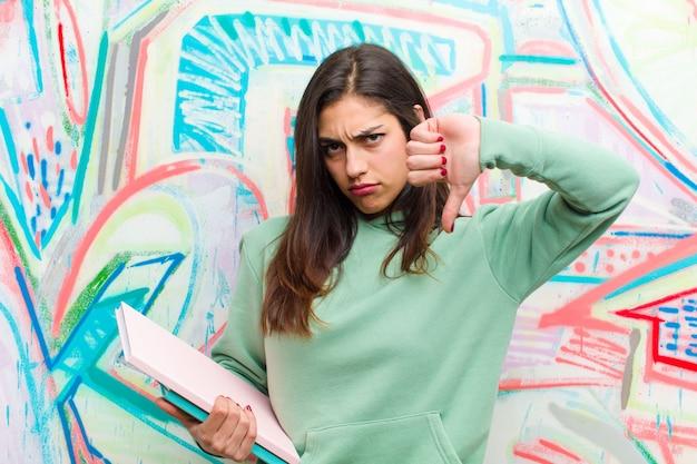 Giovane donna graziosa contro il muro di graffiti