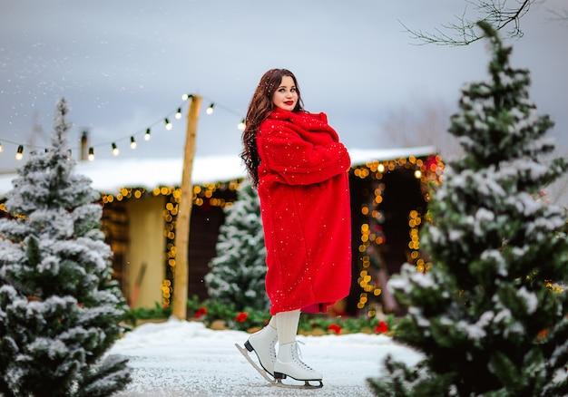 Giovane donna graziosa del brunette in cappotto lungo rosso che pattina alla pista di pattinaggio aperta. sfondo di natale.