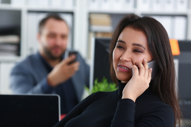 Giovane donna graziosa del brunette nel lavoro d'ufficio con il suo smartphone della stretta del capo in mani