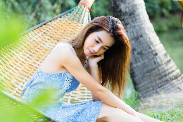 Giovane donna graziosa del ritratto che si siede in amaca