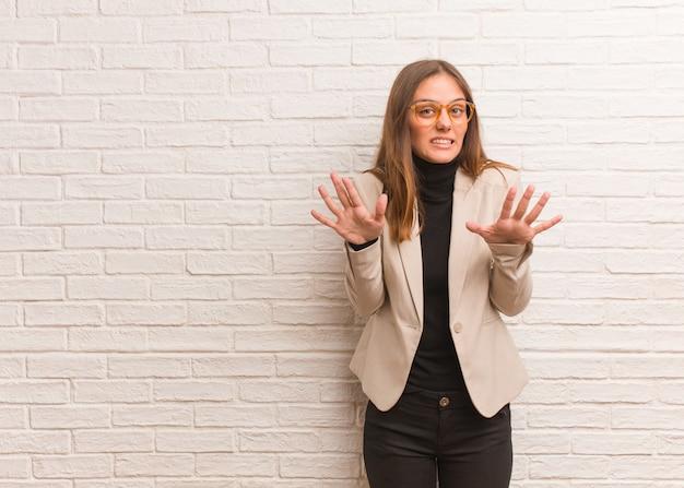 Giovane donna graziosa dell'imprenditore di affari che rifiuta qualcosa che fa un gesto di disgusto