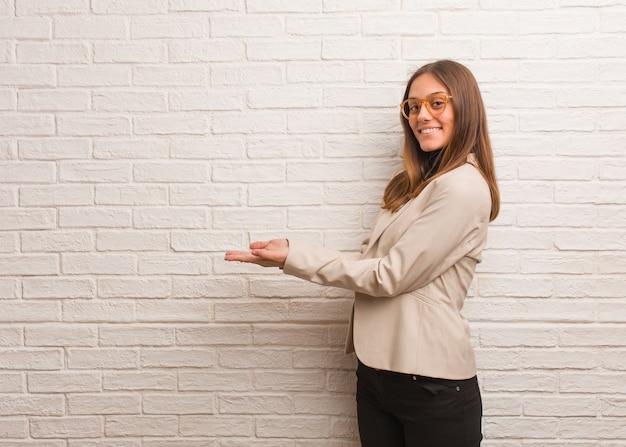 Giovane donna graziosa dell'imprenditore di affari che tiene qualcosa con le mani