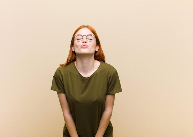 Giovane donna graziosa della testa rossa che preme le labbra insieme ad un'espressione sveglia, divertente, felice, adorabile, che invia un bacio