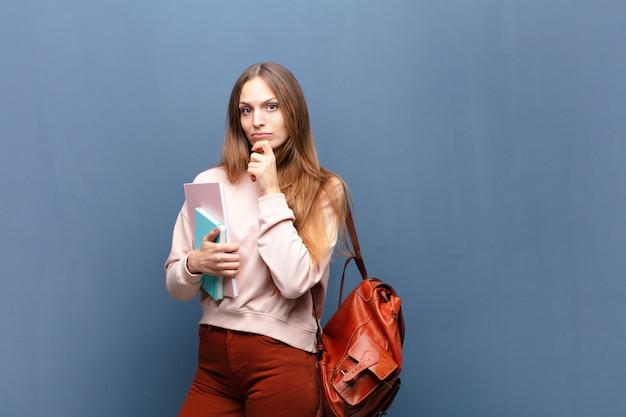 Giovane donna graziosa dello studente con i libri e la borsa contro la parete blu con uno spazio della copia