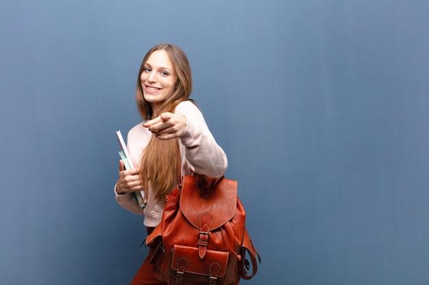 Giovane donna graziosa dello studente con i libri e la borsa