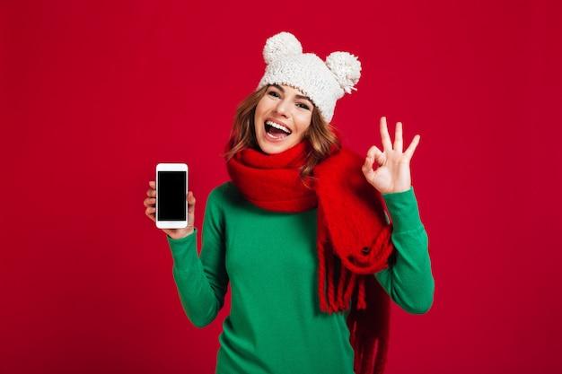 Giovane donna graziosa emozionante che mostra esposizione del telefono