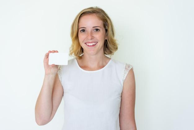 Giovane donna graziosa felice che mostra biglietto da visita in bianco