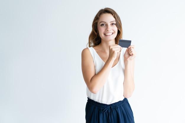 Giovane donna graziosa felice che mostra carta di plastica in bianco