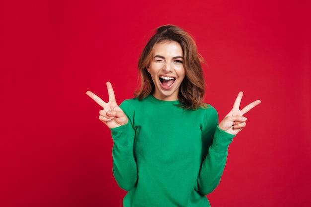Giovane donna graziosa felice che mostra gesto di pace.