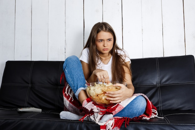 Giovane donna graziosa, guardare la tv, seduto sul divano di casa.