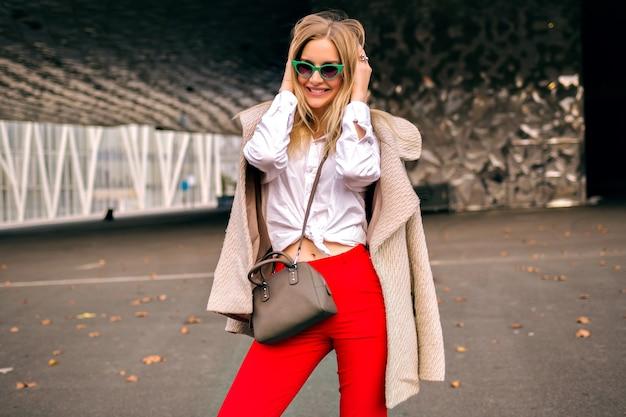 Giovane donna graziosa hipster in posa per strada vicino a moderni centri commerciali, indossando abiti da ufficio alla moda e cappotto di cashmere, inviando un bacio e godendosi una fresca giornata autunnale, colori tonica.