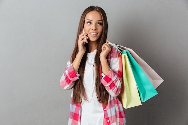 Giovane donna graziosa in abbigliamento casual, parlando al telefono cellulare, tenendo le borse della spesa, guardando lontano