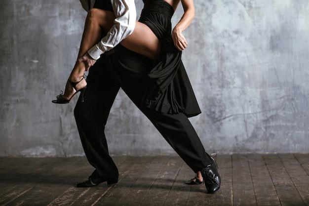 Giovane donna graziosa in abito nero e uomo che balla il tango