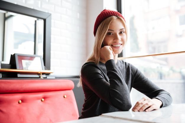 Giovane donna graziosa in cappello rosso