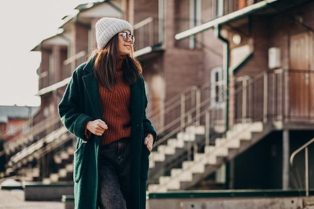 Giovane donna graziosa in cappotto caldo vicino alla casa