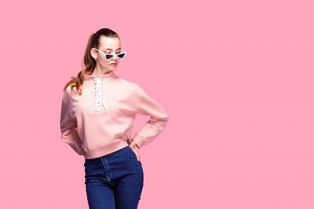 Giovane donna graziosa in maglione rosa e occhiali da sole