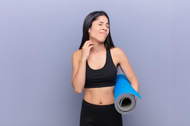 Giovane donna graziosa in ritardo con una stuoia di yoga contro il muro di cemento
