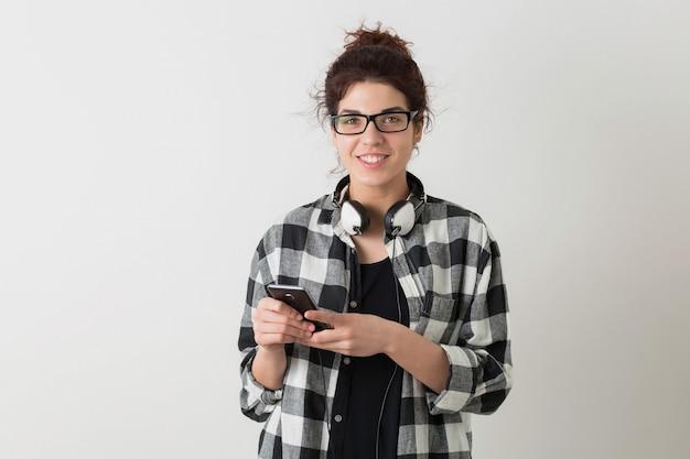 Giovane donna graziosa in vetri, tenendo smartphone, utilizzando il dispositivo digitale, sorridente, felice, cuffie, isolato, camicia a scacchi, studente, guardando