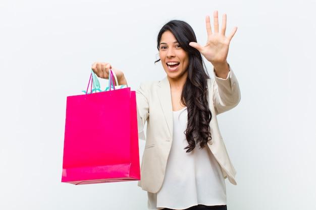 Giovane donna graziosa ispanica con i sacchetti della spesa