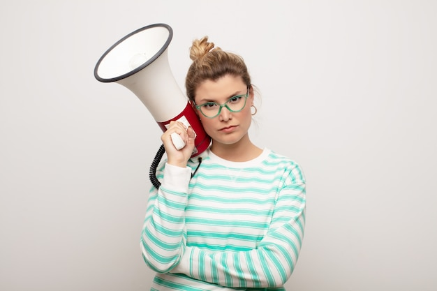 Giovane donna graziosa latina contro la parete piana con un megafono