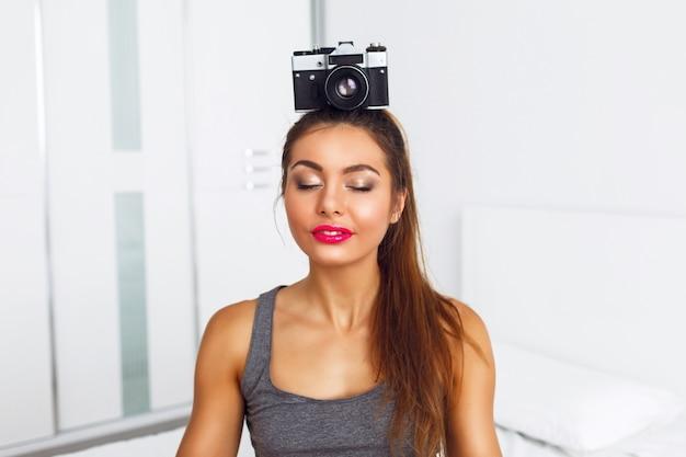 Giovane donna graziosa medita con la macchina fotografica d'epoca sulla sua testa