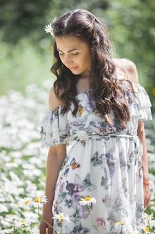 Giovane donna graziosa nel campo della camomilla. bella ragazza con fiori