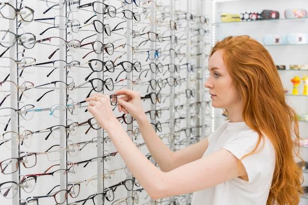 Giovane donna graziosa nel deposito di ottica che sceglie gli occhiali