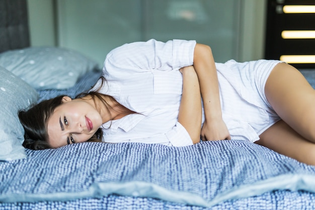 Giovane donna graziosa nel dolore che si trova sul letto