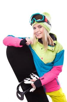 Giovane donna graziosa nello snowboard della tenuta dell'attrezzatura dello sci