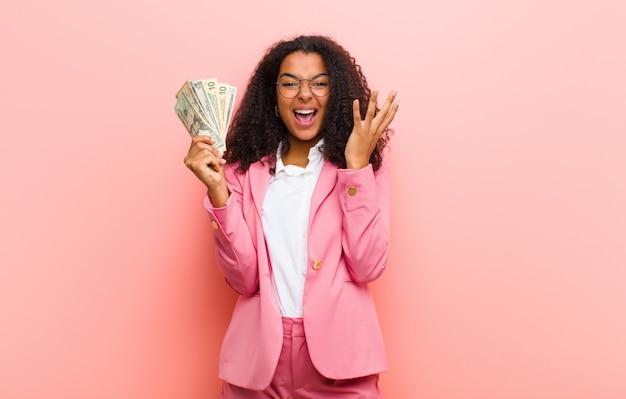 Giovane donna graziosa nera con banconote in dollari contro il muro rosa